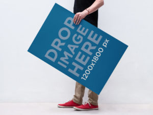 Free PSD of a Man Holding a Poster Mockup